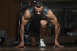 Strong Muscular Men Kneeling On The Floor - Almost Like Sprinter Starting Position